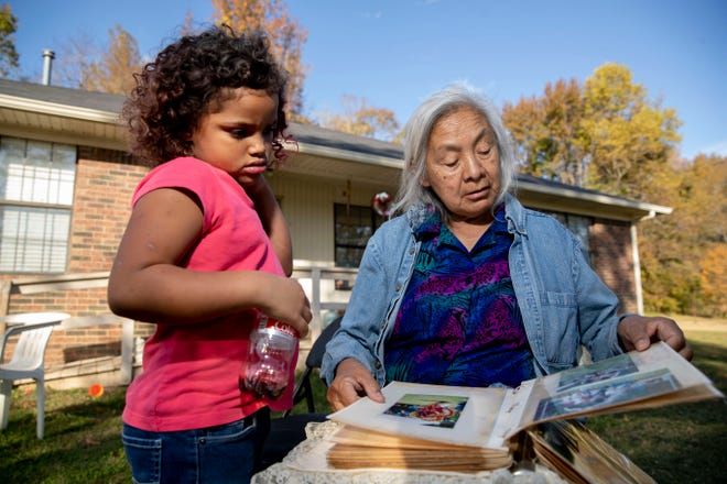 Lacie Bell looks through a photo album with her granddaughter, Emani, 4, on Thursday, Nov. 5, 2020, at the Choctaw reservation in Henning, Tennessee.