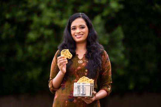 "Ranjani Venkatakrishnan's poses for a portrait while holding a bowl of murukku at the Venkatakrishnan's home on Nov. 5, 2020 in Chandler, Arizona. Ranjani plans on sharing her mom's recipe for murukku on the Blaze radio show ""Desi Tunes"" that she hosts for Diwali."