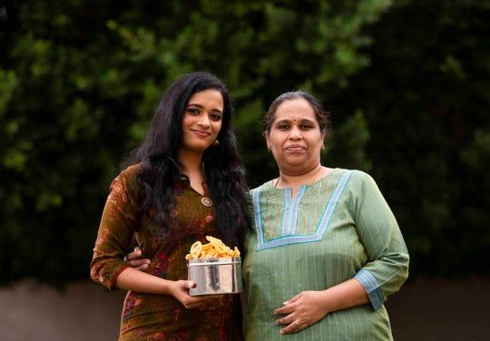 "Ranjani Venkatakrishnan and her mother, Anuradha Venkatakrishnan, pose for a portrait while holding a bowl of murukku at the Venkatakrishnan's home on Nov. 5, 2020 in Chandler, Arizona. Ranjani plans on sharing her mom's recipe for murukku on the Blaze radio show ""Desi Tunes"" that she hosts for Diwali."