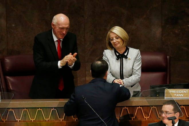 In this Jan. 13, 2020, photo, Arizona Republican Gov. Doug Ducey (center) shakes hands with Senate President Karen Fann, R-Prescott, as House Speaker Rusty Bowers, R-Mesa, applauds after Ducey delivered his State of the State address at the Capitol in Phoenix.