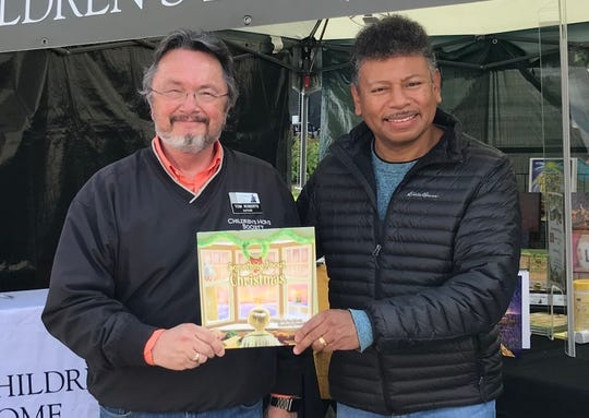 "Author Tom Roberts (left) and illustrator Hector Curriel (right) pose with their new book, ""Something About Christmas,"" to raise funds for the Children's Home Society."