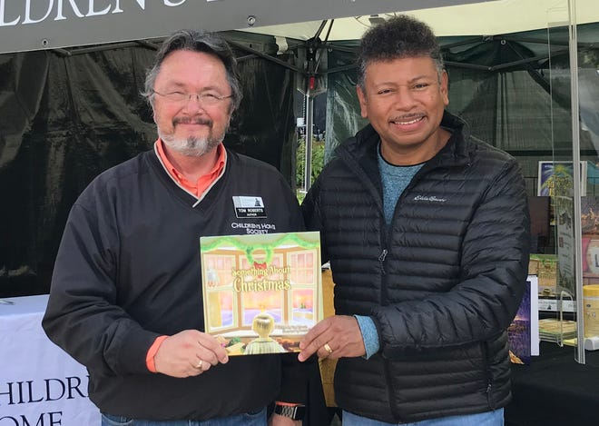 """Author Tom Roberts (left) and illustrator Hector Curriel (right) pose with their new book, """"Something About Christmas,"""" to raise funds for the Children's Home Society."""