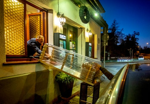 A box with food slides down to car from a window of the apple cider restaurant 'Zum Lahmen Esel' in Frankfurt, Germany, Thursday, Nov.5, 2020. Due to the new partial lockdown to avoid the coronavirus spread the restaurant which has been in operation since 1807 offers cider and food to go in a self-made drive through set up.
