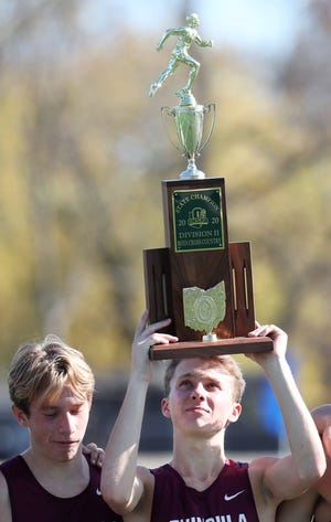 Ryan Champa Woodridge holds the championship trophy for Div. II 2020 Cross Country State Championship at Fortress Obetz and Memorial park in Obetz, Ohio  on Saturday, Nov. 7, 2020. Champa finished first in the event and Woodridge team placed first.  [Mike Cardew/Beacon Journal]