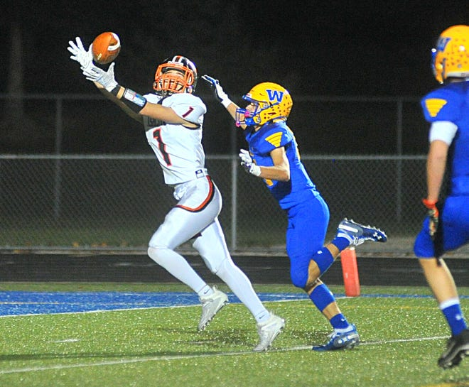 Ashland's Landon McFrederick reaches out to make a catch during high school football action against Wooster on Friday night at Follis Field. The Arrows won, 46-35.