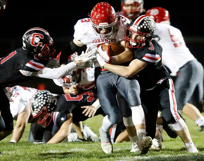Johnstown's Wes Myers (3) is tackled by Crestview's Adison Reymer (21) and Connor Morse (3) during the Cougars' 42-24 win Friday night at Scott Bailey Memorial Field.