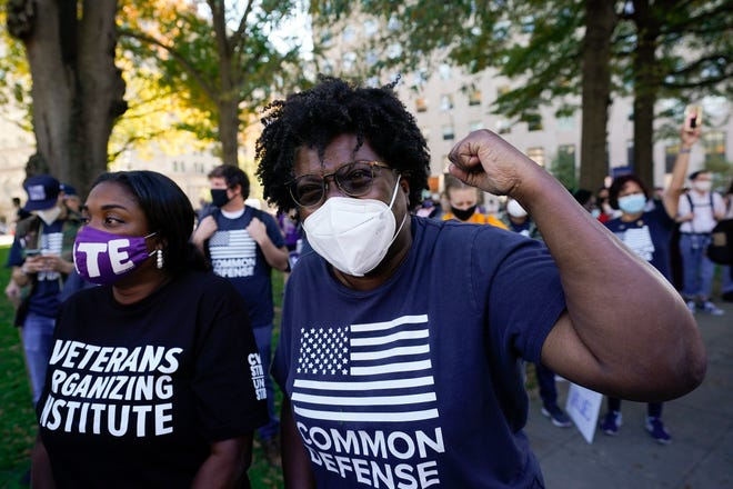 People gathered in Black Lives Matter Plaza, react to the presidential race being called in Joe Biden's favor, Saturday, Nov. 7, 2020, in Washington. Democrat Joe Biden has defeated President Donald Trump to become the 46th president of the United States.