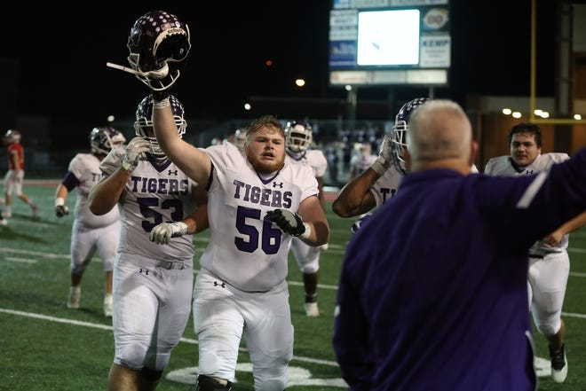 Pickerington Central lineman Brock Egan (56) leads a parade of teammates to the sideline to celebrate the Tigers' 38-31 victory over Mentor on Friday in a Division I state semifinal.