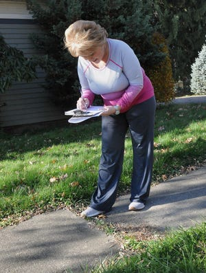 Wooster resident Beth Beatty checks the condition of sidewalks in the area looking for uneven or broken concrete.