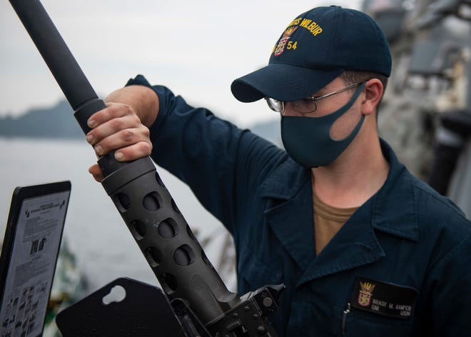 Waterford native Brady Kamper, a U.S. Navy gunner's mate seaman, attaches a barrel to a 50-caliber machine gun aboard the guided-missile destroyer USS Curtis Wilbur at Yokosuka, Japan, on Tuesday. The vessel is assigned to Destroyer Squadron 15, which is the Navy's largest forward deployed destroyer squadrons and the  U.S. 7th Fleet's principal surface force.