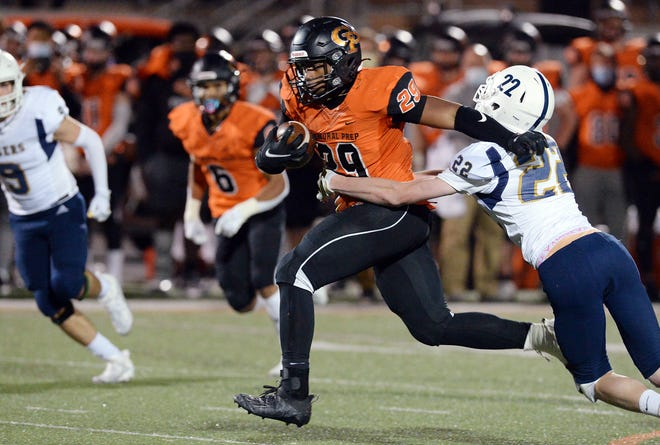 Cathedral Prep senior Jaheim Williams, center, runs near Hollidaysburg senior Rocco Grassi, right, during a PIAA Class 5A football playoff game at Dollinger Field on Nov. 6, 2020, in Erie.