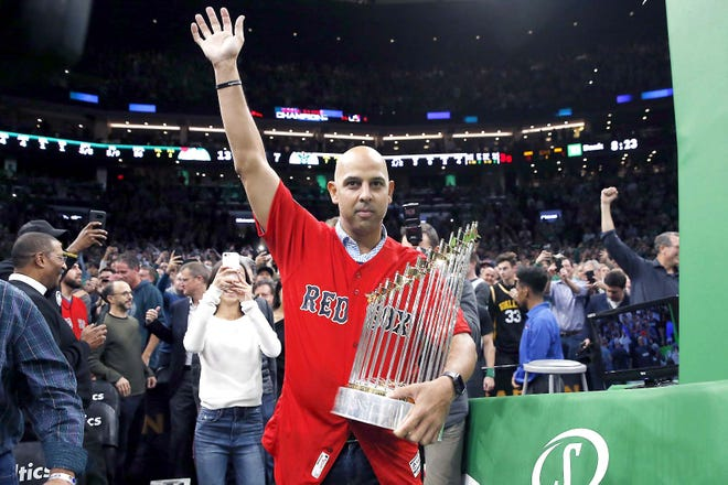Boston Red Sox manager Alex Cora waves as he walks onto the court with the baseball World Series trophy during the first half of a Nov. 1, 2018,  NBA game between the Boston Celtics and the Milwaukee Bucks in Boston. The Red Sox rehired Cora as manager Friday.