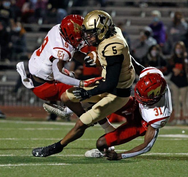 Coronado's Imari Jones (31) and Kaleb Pillow (31) tackle Lubbock High's Darin Mendez (5) during a District 2-5A, Division I game, Friday, Nov. 6, 2020, at PlainsCapital Park at Lowrey Field.
