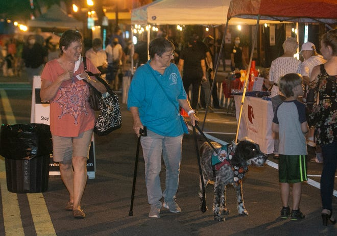 Jo Anna Pyle, left, and friend Cathie Williams along with her 10-year-old English setter, Gracie, stroll along Kentucky Avenue during the Dog Days Downtown themed First Friday in Lakeland on Friday night. The event sponsored by the Lakeland Downtown Development Authority resumed normal activity after a lengthy hiatus due to the COVID-19 pandemic.