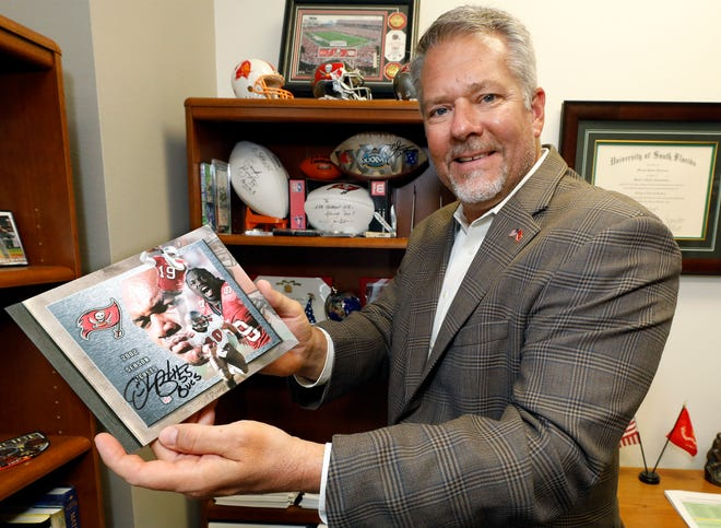 Shawn Sherrouse holds his 2002 Tampa Bay Buccaneers season ticket book from the team's Super Bowl championship season signed by Hall of Fame linebacker Derrick Brooks at city hall in Lakeland. A native of Polk County, Sherrouse was officially named Lakeland's city manager on Nov. 2.