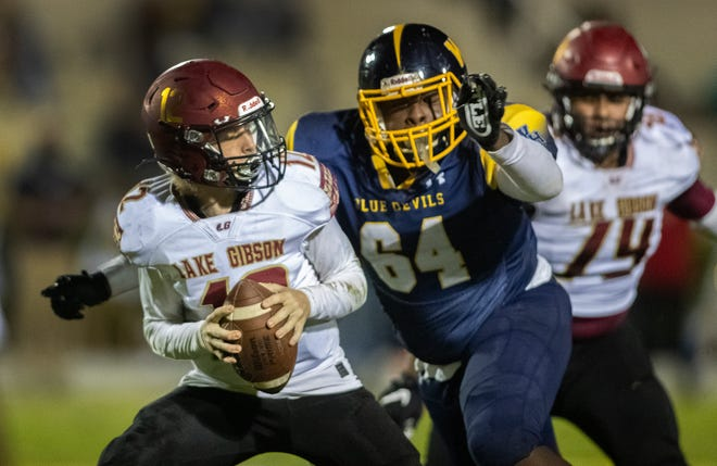 Winter Haven Rashaun Saint-Aime (64) closes in on Lake Gibson quarterback Logan Hackett (12) in first-half action at Denison Stadium last week. Winter Haven plays host to Lakeland, while Lake Gibson plays host to Spoto in play-in games on Friday.