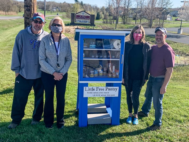 Victor residents John and Pat Stewart and Teri and Kevin Graham show off their active community-sponsored Little Free Pantry.