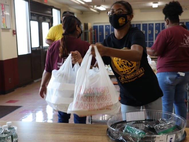 Amiyah Evans, a Mohawk Valley Junior Frontiers member, picks up packaged meals during the Mohawk Valley Frontiers Club Thanksgiving Dinner Giveaway. The annual dinner was delivered or offered as carry-out this year to follow social distancing guidelines.