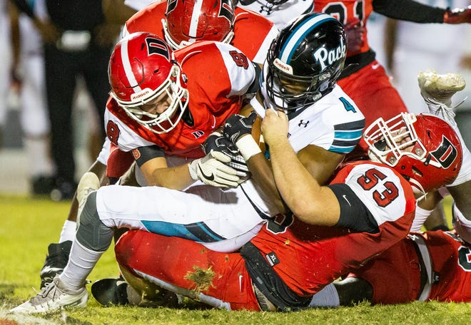 Dunnellon's Sam Wryals and Colby Smith bring down West Port's Or'Donte Miller in the second quarter. The Dunnellon Tigers defeated the West Port Wolf Pack 35-0 Friday night.