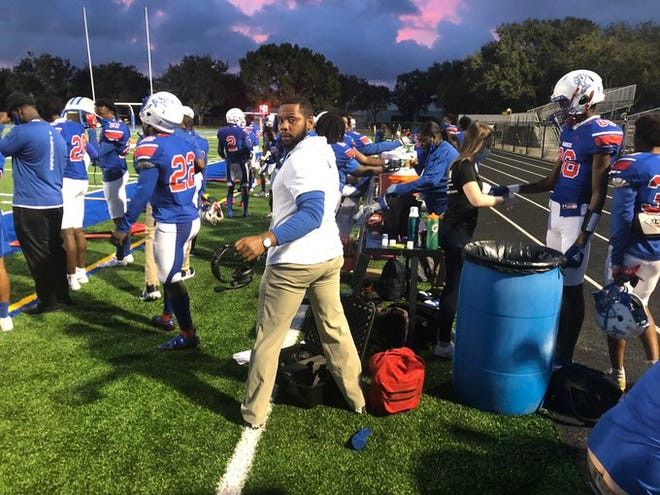 Pahokee coach DJ Boldin (white shirt) prepares his Blue Devils for Friday's game against Wellington. Pahokee won 22-16 in overtime.