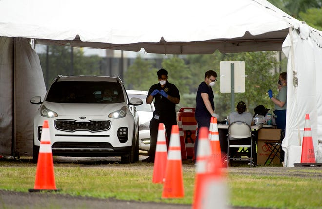 Workers test motorists Saturday for coronavirus at a drive-thru rapid testing site at the FITTEAM Ballpark of the Palm Beaches in West Palm Beach. The site would shut down after Saturday until the passage of Tropical Storm Eta.