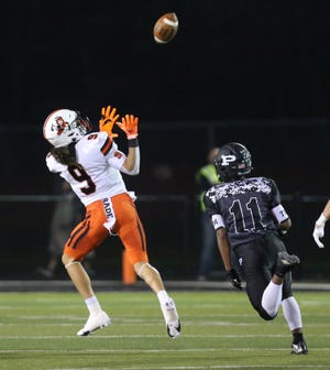 Jayden Ballard (9) of Massillon hauls in a touchdown catch while being trailed by Camron Hall (11) of Perry during the DII regional final at Perry on Friday, Nov. 6, 2020.