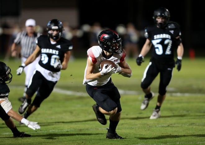 Creekside receiver Jack Goodrich, center, makes a catch and run in the first quarter Friday night, Nov. 6, 2020, at Ponte Vedra.