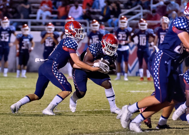 Manatee High quarterback Jayse Berzowski hands the ball off to running back Kyree Jones for a first quarter touchdown against Southeast High at Hawkins Stadium in Bradenton Friday night.