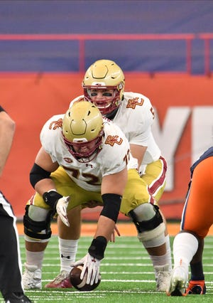 Boston College quarterback Phil Jurkovec calls signals under former Shepherd Hill standout Alec Lindstrom (72) in the first quarter against Syracuse.