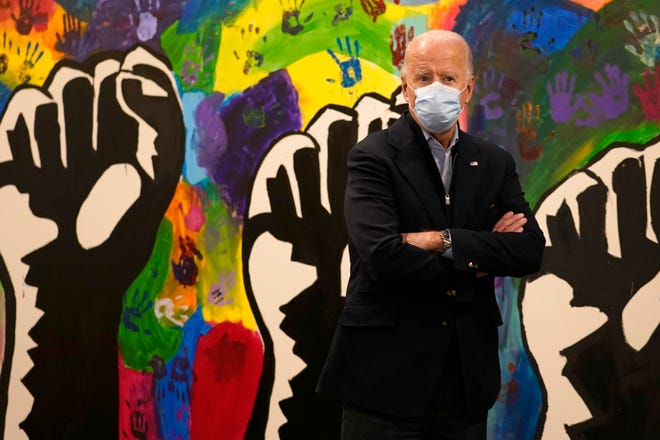 In this Nov. 3  file photo, Democratic presidential candidate former Vice President Joe Biden pauses in front of a mural during visit to The Warehouse teen center in Wilmington, Del.
