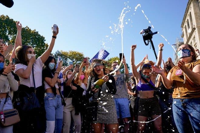 Amanda Madden sprays champagne as people celebrate at Black Lives Matter Plaza after CNN called the race in favor of Democratic presidential candidate Joe Biden over Pres. Donald Trump to become the 46th president of the United States Saturday in Washington.