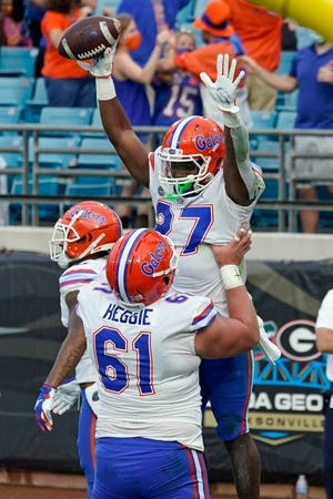 Florida running back Dameon Pierce (27) celebrates his two-yard touchdown run against Georgia with offensive lineman Brett Heggie (61) during the first half Saturday in Jacksonville.