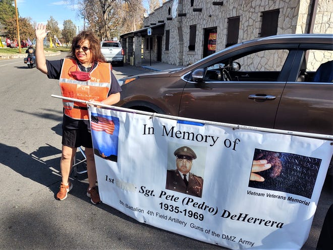Ava DeHerrera waves to a passing motorist during Saturday's reverse Veterans Day Parade in Mineral Palace Park.