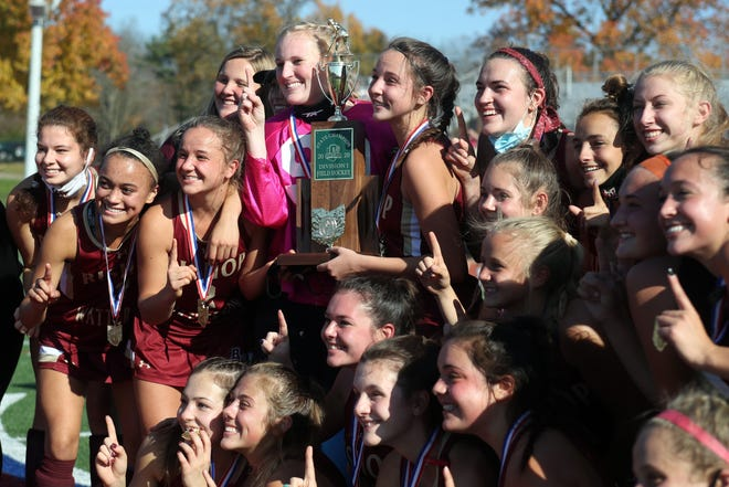 Watterson field hockey players and coaches pose for a photo with the state championship trophy after defeating Hudson 3-0 on Nov. 7 at Thomas Worthington.