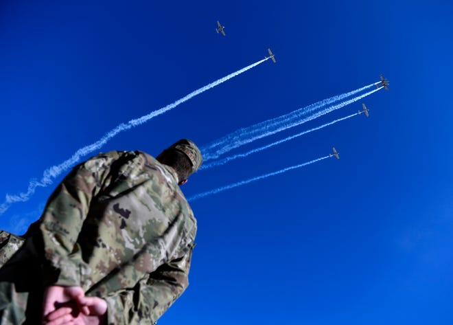 A Dyess Air Force Base airman stands at parade rest as a missing-man formation flies overhead during Saturday's Veterans Day parade in downtown Abilene.
