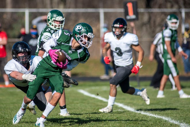 Pennfield junior Luke Davis (5) breaks away from pressure and scores a touchdown on Saturday, Nov. 7, 2020 at Pennfield High School.