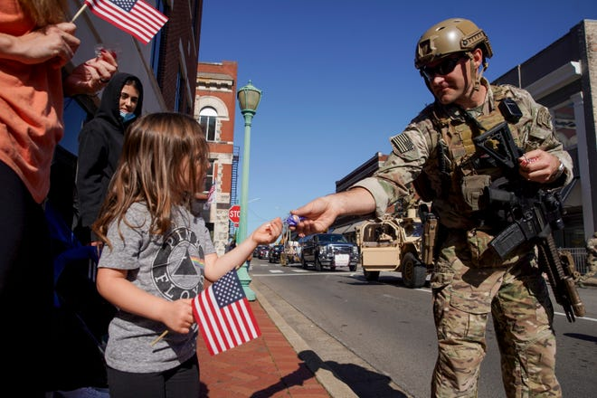 A soldier hands out candy to Soleil Hicks, 3, left, during the Veterans Day Parade at the Montgomery County Historic Courthouse in Clarksville, Tenn., on Saturday, Nov. 7, 2020.