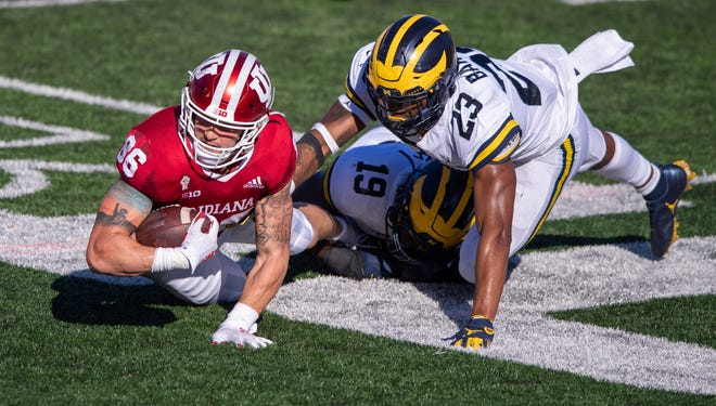 Indiana tight end Peyton Hendershot (86) dives for first-down yardage as he's stopped by Michigan defensive lineman Kwity Paye (19) and linebacker Michael Barrett (23) during the second half.