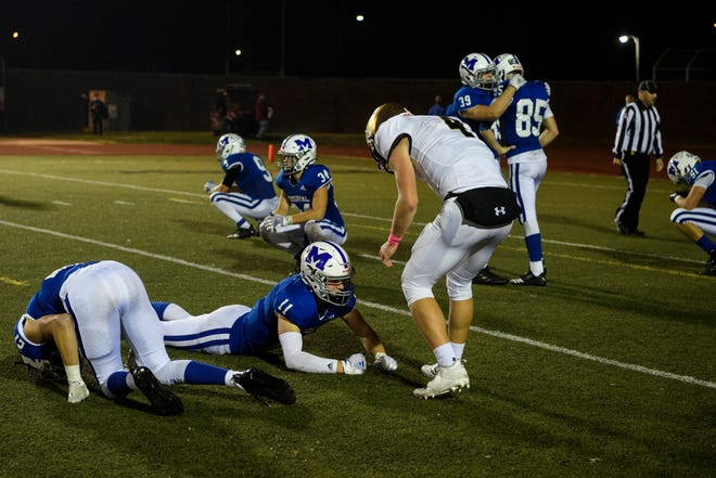 Central's Blake Herdes (4) offers to help up Memorial's Leo Collins (11) just after the Tigers' 30-21 loss in the Class 4A Sectional 24 final on Friday night at Enlow Field.