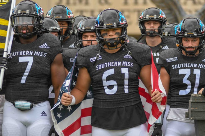 Russ Green, Southern Miss offensive lineman, drapes an American flag over his shoulders before entering the field for their NCAA football game against the University of Alabama at USM in Hattiesburg, Miss., Saturday, Nov. 7, 2020.