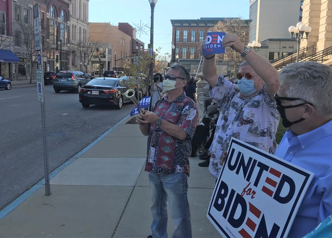 Albert Urazaev, from left, Robert Jones and Joe Mackey celebrate Joe Biden's victory in the presidential race Saturday, Nov. 2, 2020, in downtown Lafayette, about an hour after the race was called in the Democratic candidates' favor. A group of 20 Biden supporters honked horns and played instruments for passing drivers in front of the Tippecanoe County Courthouse.