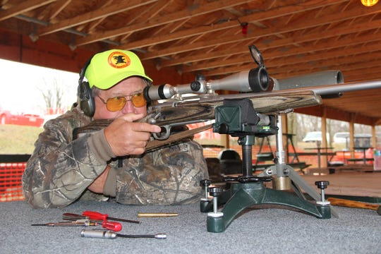 Roger Scheel, a member of Daniel Boone Conservation League in Hubertus, Wis., looks through a rifle scope during a sight-in clinic at the club's shooting range.