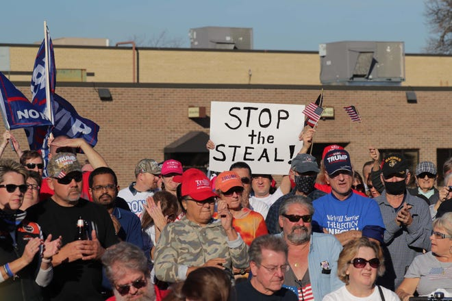 Donald Trump supporters hold signs at a rally for Trump at American Serb Hall on West Oklahoma Avenue Saturday in Milwaukee.
