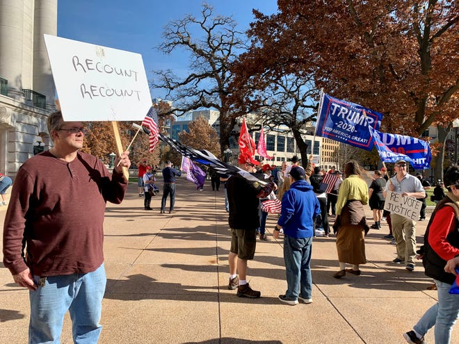 """Mike Zaremba, left, was part of a group of protesters at the Wisconsin state Capitol for a post-election rally to protest Joe Biden's victory. """"When I hear Trump announce the election is over and he's either won or conceded, that's when I'll believe it,"""" Zaremba said."""