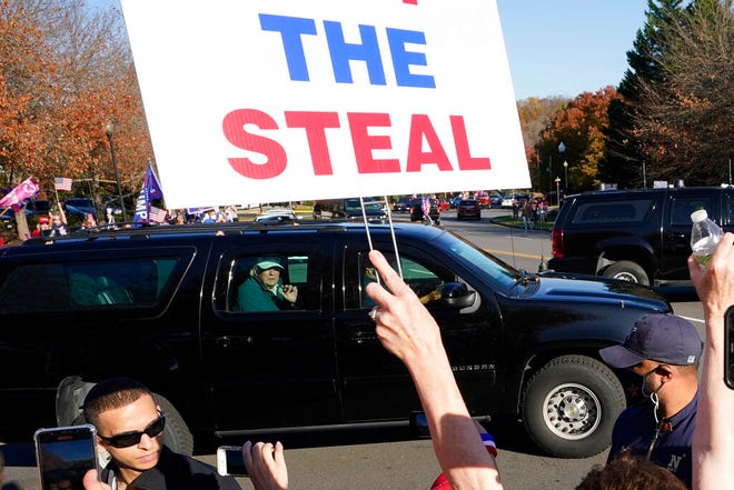 President Donald Trump looks on to supporters after leaving the Trump National golf club in Sterling, Va., Saturday, Nov 7, 2020. (AP Photo/Steve Helber)