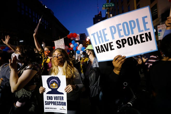 Demonstrators stand outside the Pennsylvania Convention Center where votes are being counted, Friday, Nov. 6, 2020, in Philadelphia. (AP Photo/Rebecca Blackwell)