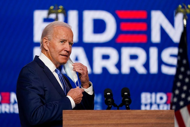 Democratic presidential candidate former Vice President Joe Biden removes his face mask as he arrives to speak, Friday, Nov. 6, 2020, in Wilmington, Del. (AP Photo/Carolyn Kaster)