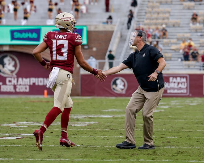 Florida State head coach Mike Norvell shakes the hand of quarterback Jordan Travis after scoring a touchdown during the game against the Pittsburgh Panthers at Doak Campbell Stadium on Bobby Bowden Field on November 7, 2020 in Tallahassee, Florida.