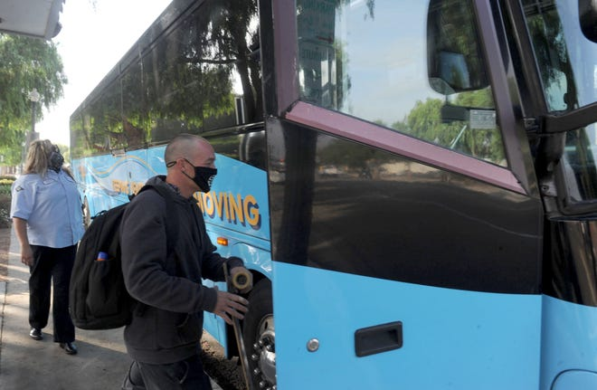 Bus driver Marisa Suarez, left, of the Ventura County Transportation Commission, watches AJ Madrid hop on her bus at the Moorpark Metrolink Station on Friday, Nov. 6, 2020.