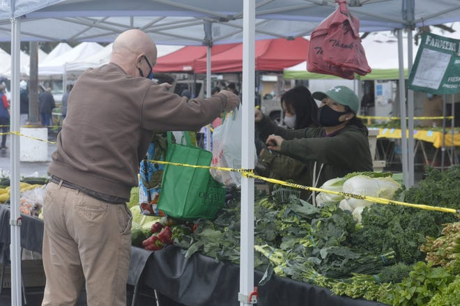 Xaxeng Thao, right, of Mao Farms bags vegetables on Saturday at the Visalia Farmers Market.